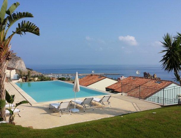 residence-magara-cefalu-sicilie-zwembad-ligstoelen-palmbomen.jpg