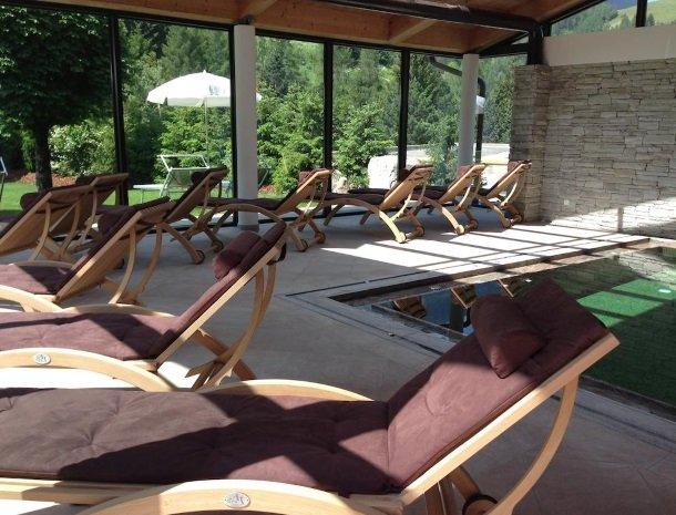 hotel-arnaria-ortisei-trentino-binnenzwembad-ligstoelen.jpg